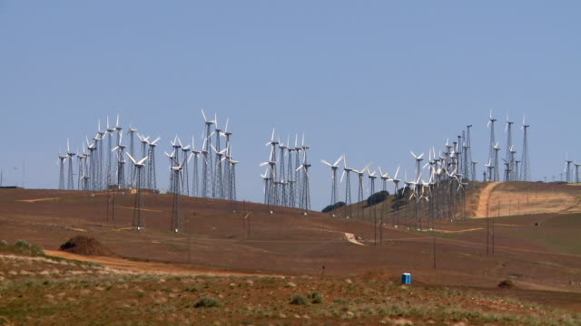 a row of wind turbines rotate on a wind farm. - turbine stock-videos und b-roll-filmmaterial
