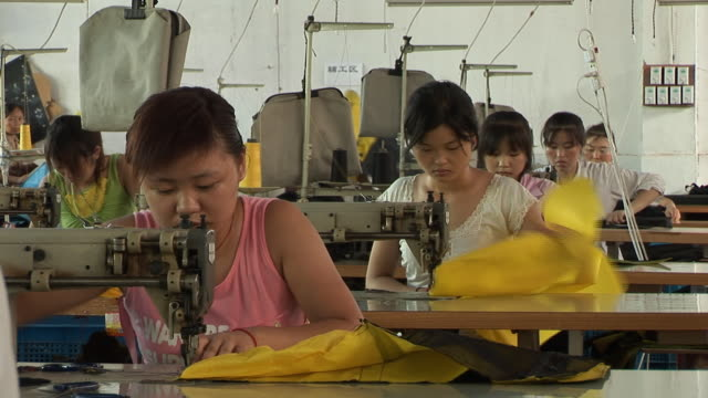 ms row of woman working on sewing machines in factory/ shanghai, china - textile stock videos & royalty-free footage