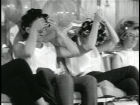 B/W 1965 PAN row of women in curlers sitting under hair dryers in beauty parlor / documentary