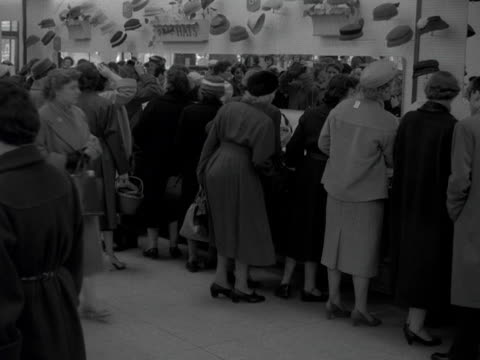 row of women try on hats in a department store. 1957. - department store stock videos & royalty-free footage
