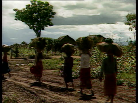 row of women walk past and away from camera with bags and packages on their heads wooden huts of village in background cambodia - cambodia stock videos and b-roll footage