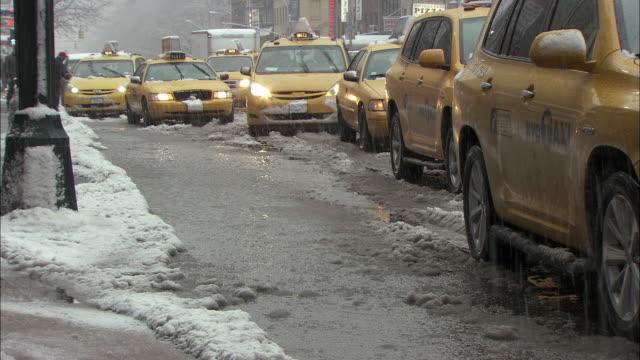 ms row of yellow cabs on snowy street / new york city, new york, usa - slush stock videos and b-roll footage