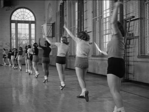 vidéos et rushes de b/w 1953 row of young women in gymnasium practicing baton twirling routine / documentary - film documentaire image animée