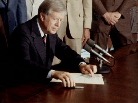 row over billy carter's links with libya; usa: washington dc: int us president jimmy carter signs papers pull out stands up carter - jimmy carter us president stock videos & royalty-free footage