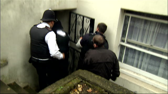 row over policing of riots and bill bratton advisory role england london ext police officers shouting 'police stay where you are' as entering front... - basement stock videos and b-roll footage