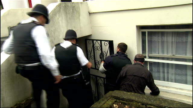row over policing of riots and bill bratton advisory role london police raiding basement flat police inside flat seen through window - basement stock videos and b-roll footage