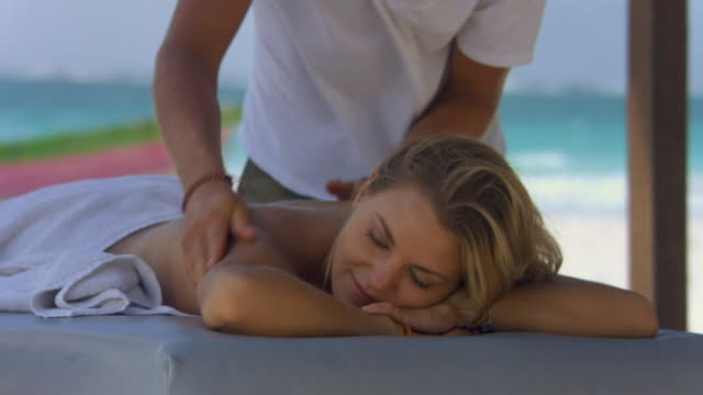 SM MS RACK FOCUS/ Rowboat on sandy beach as woman gets massage in foreground/ Tulum, Mexico