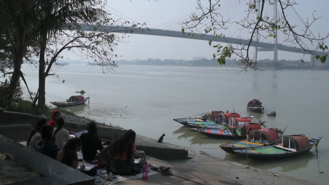 rowboats and people sitting on hooghly river bank with second hooghly bridge in view in kolkata, west bengal, india, on monday, december 7, 2020. - hooghly river stock videos & royalty-free footage