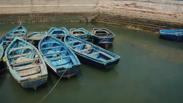 vidéos et rushes de ms pan rowboats moored in harbor/ morocco - groupe moyen d'objets
