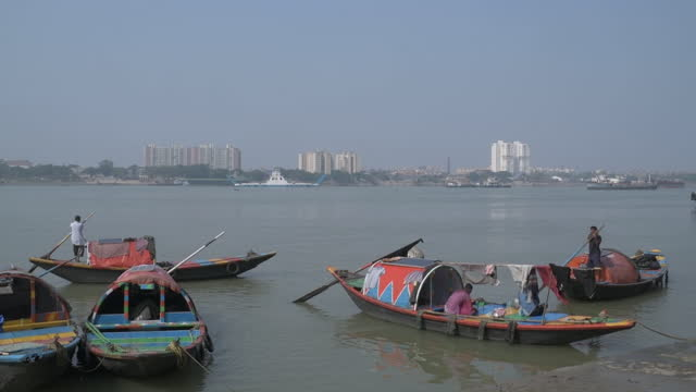 rowboats moored on hooghly river in kolkata, west bengal, india, on monday, december 7, 2020. - hooghly river stock videos & royalty-free footage