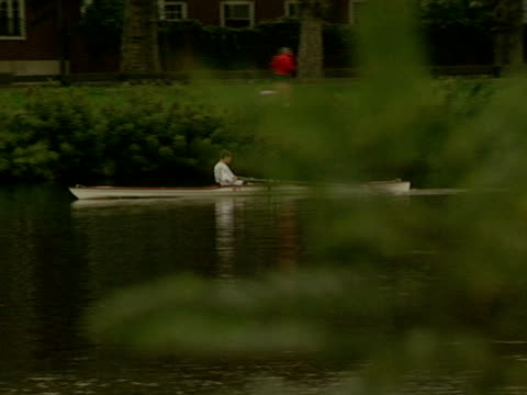 a rower on the charles river travels past harvard's eliot house tower - charles river stock videos & royalty-free footage