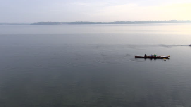 Rowers propel sculls on a lake.