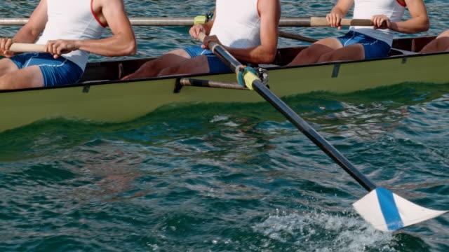 athleten die ruder durch das wasser bewegt und treibt das boot rudern - rudern stock-videos und b-roll-filmmaterial