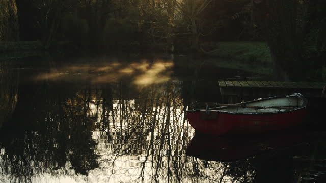 rowing boat at a pier with mist moving on a lake in a magical peaceful calm atmospheric countryside scene in a beautiful garden, english countryside scene of lakes and trees, england - jetty stock videos & royalty-free footage
