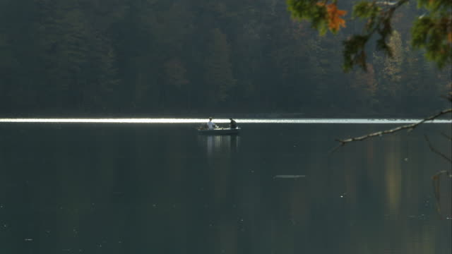 a rowing boat in the disatnce on a still lake at green lakes state park in new york. available in hd. - rowing boat stock videos & royalty-free footage