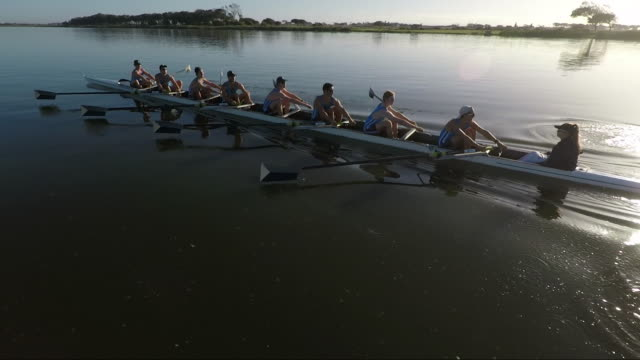rowing eight team training on a lake at sunrise - rudern stock-videos und b-roll-filmmaterial
