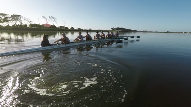 Rowing eight team training on a lake at sunrise