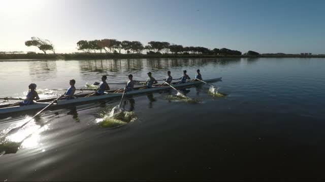 vidéos et rushes de rowing eight team training on a lake at sunrise - s'impliquer à fond