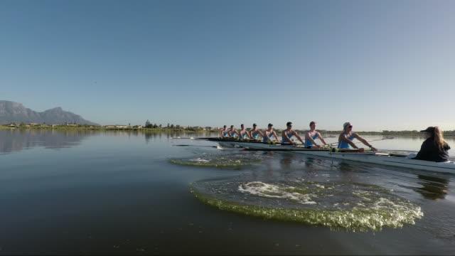 vídeos y material grabado en eventos de stock de rowing eight team training on a lake at sunrise - grupo organizado