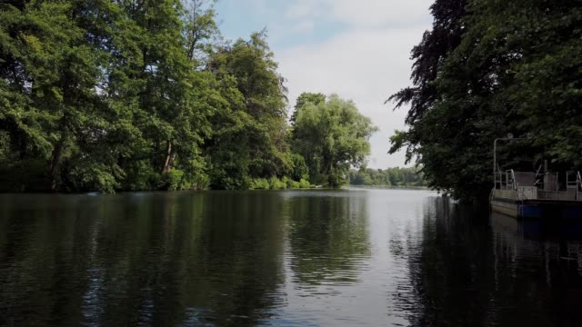 rowing on a river. tranquil scene. river landscape with boat, blue sky, clouds, trees by the water (rudern auf dem fluss wakenitz in lübeck) - tina terras michael walter stock videos & royalty-free footage