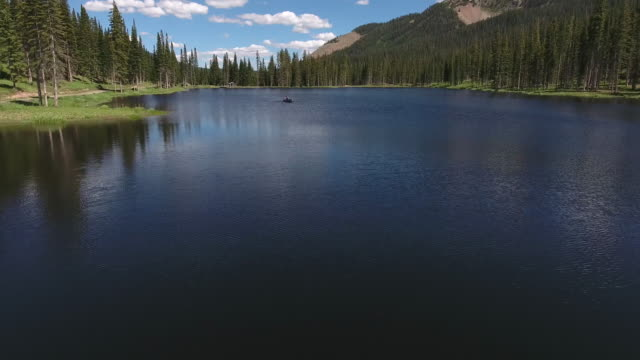 stockvideo's en b-roll-footage met rowing on mountain lake orbit , rocky mountains reveal fall colors lake reflection, off road, rzr wildlife, foliage short aerial, 4k, 19s, stock video sale - drone discoveries - drone aerial view - sale