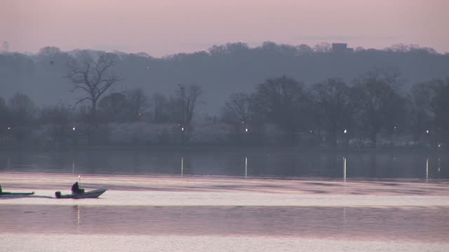 ws, rowing team on river at dusk, potomac river, washington dc, washington, usa - 後を追う点の映像素材/bロール