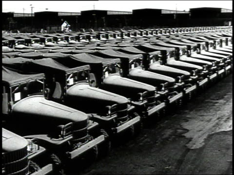 vídeos de stock e filmes b-roll de 1942 pan rows of army trucks in lot / detroit, michigan, united states - 1942