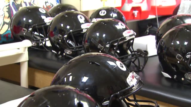 rows of black football helmets at a riddell testing lab in rosemont, ill. - アメリカンフットボールヘルメット点の映像素材/bロール