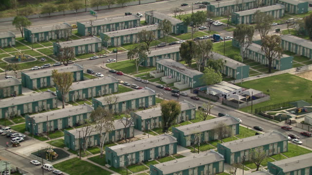 rows of blue and white apartment buildings at the imperial courts public housing development in watts, los angeles. - 公営アパート点の映像素材/bロール