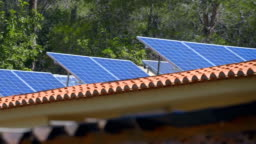 Rows of blue color solar panels on a tiled roof in Spain tilted toward the sun