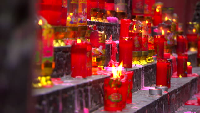 rows of candles flicker at the arhat buddhist temple in chongqing.  - votive candle stock videos and b-roll footage