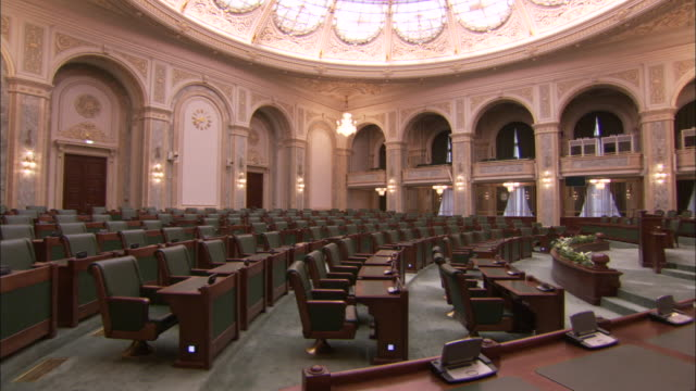 rows of chairs face the central podium in the senate chamber in the romanian palace of parliament. available in hd - senate stock videos and b-roll footage