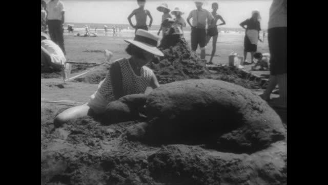 vidéos et rushes de rows of children on the beach digging holes for sand castle contest / individual children scoop and shape sand / judges mill about observing progress... - concurrent