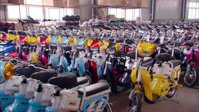 MS TD Rows of colorful electric bicycles sitting on floor of Aihu electric bicycle factory, Tianjin, Tianjin, China