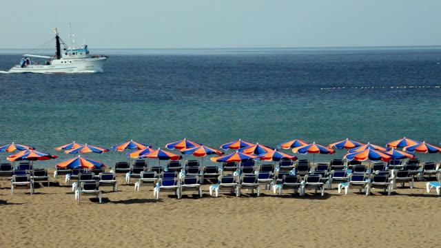 vidéos et rushes de ws rows of deckchairs facing ocean on beach, trawler in background, lanzarote, canary islands - transat