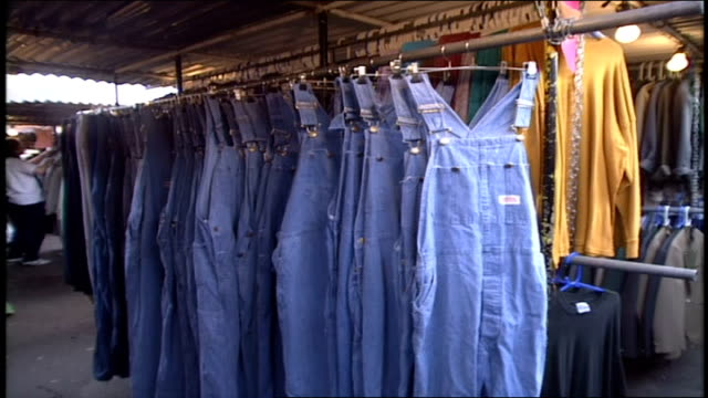 rows of denim overalls on display at camden market - dungarees stock videos & royalty-free footage