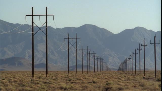 vídeos y material grabado en eventos de stock de ws, pan, rows of electricity poles in desert with mountains in background, tonopah, nevada, usa - poste telegráfico