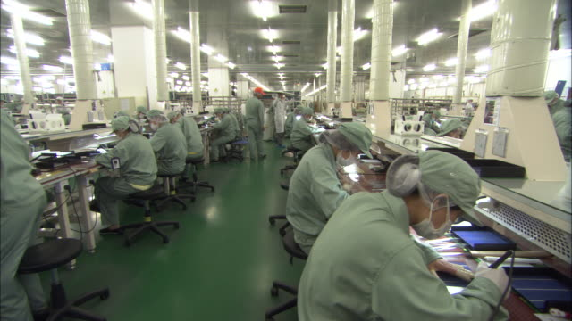 WS DS Rows of employees working on solar panels in Suntech Power Holdings factory, Wuxi, Jiangsu, China