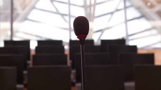 vídeos de stock, filmes e b-roll de rows of empty seats face a microphone in a courtroom. - equipamento de mídia