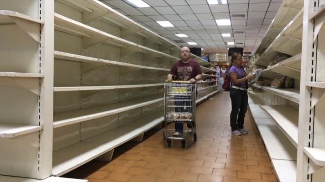 vídeos de stock, filmes e b-roll de rows of empty shelves fill venezuelan supermarkets after the government forced more than 200 establishments to lower prices amid spiralling... - venezuela