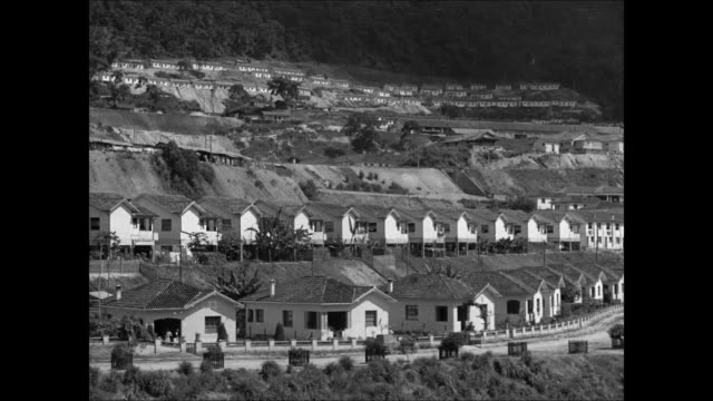 Rows of government houses on hill side LA MS Two Brazilian women hanging laundry MS Couple walking by new houses
