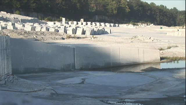 rows of granite blocks are staged at the base of a hill near a quarry. - granite stock videos and b-roll footage