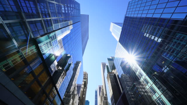 vidéos et rushes de rows of high-rise buildings shine by sunlight and surround the 42nd street midtown manhattan new york city. - quartier de bureaux