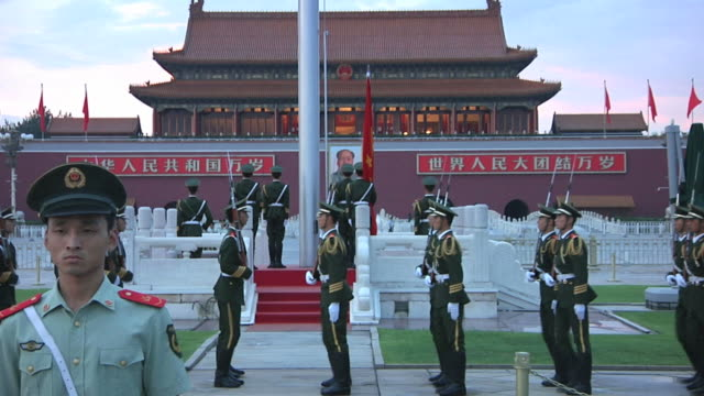 vídeos de stock e filmes b-roll de ws rows of honor guards marching around platform during flag lowering ceremony in tiananmen square / beijing, china - soldado exército