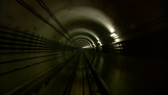 vidéos et rushes de rows of lights, electrical conduits, and railway tracks line the interior of a subway tunnel. - tunnel