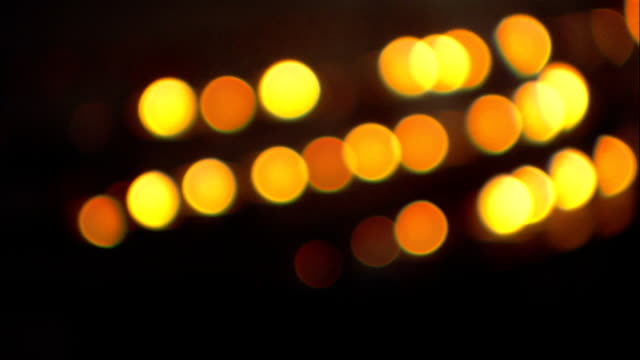 rows of lit candles flicker in a darkened cathedral. - candlelight stock-videos und b-roll-filmmaterial