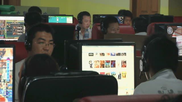 MS Rows of men at computers in internet cafe / Yangzhou, Jiangsu, China