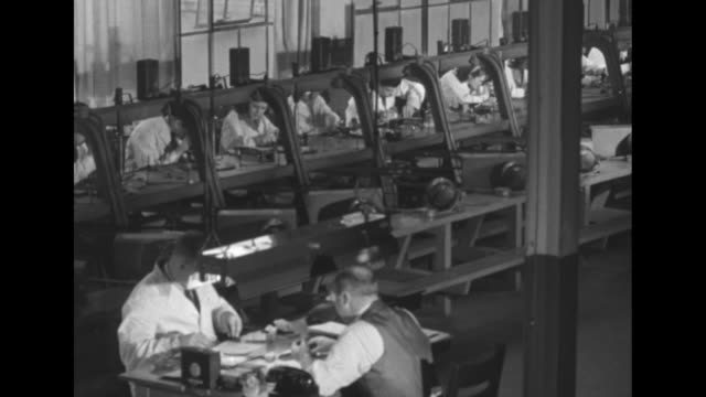 rows of men & women at workstations with belt driven grinders work with diamonds / man carefully grinds edge of very small diamond / grinding / pan... - clamp stock videos & royalty-free footage