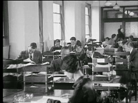 stockvideo's en b-roll-footage met b/w 1927 rows of men + women working at desks in office / industrial - men