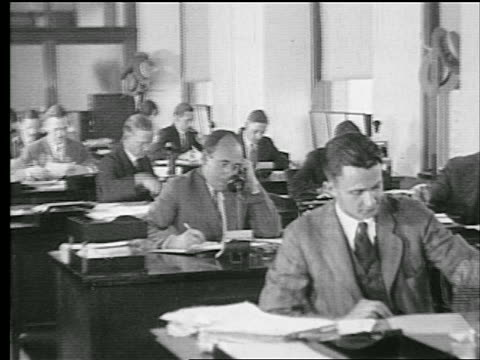 B/W 1927 rows of men working at desks / one man on telephone / industrial